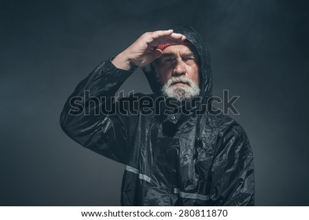 Portrait of a Bearded Middle Age Man with Facial Hair, Wearing Black Rain Jacket, Looking Afar with a Serious Facial Expression.