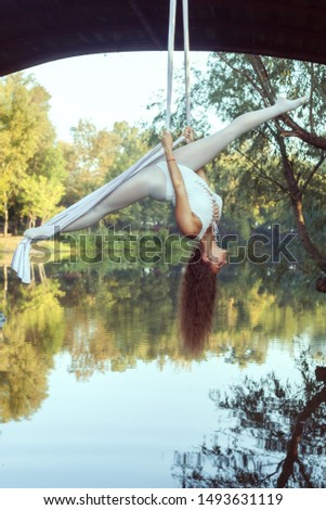 Portrait of a beautiful acrobat on canvases over the river. She does the splits.