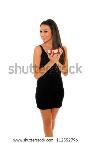 Portrait of a beautiful adult woman in black dress holding a gift box posing over white background