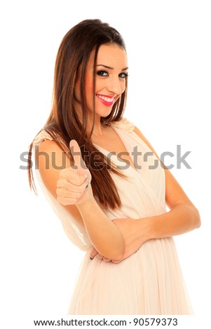 Portrait of a beautiful adult woman in dress posing with her thumb up  over white background