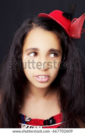 Portrait of a beautiful African little girl on black background #667702609