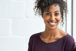 Portrait of a beautiful african woman smiling. Young black woman in casual looking at camera with copy space. Portrait of cheerful girl with afro hair sitting near a window.