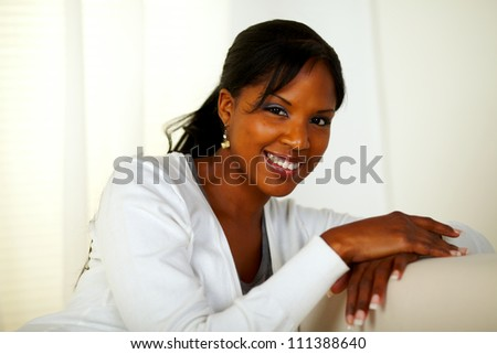 Portrait of a beautiful afro-American woman smiling at you at soft colors composition - stock photo