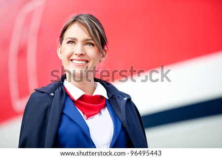 Portrait of a beautiful air hostess with a airplane at the background