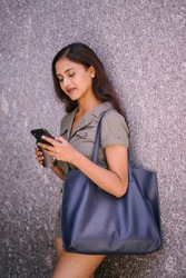 Portrait of a beautiful and attractive Indian Asian young woman smiling as she checks her smartphone. She is leaning against a wall in a city in the day and is smiling as she uses her device.