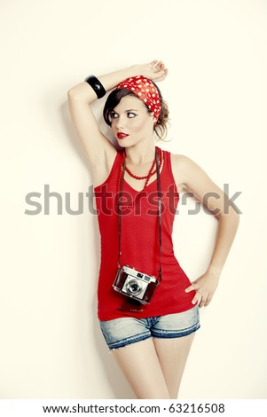 Portrait of a beautiful and fashion young woman with a photographic camera