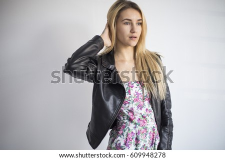 Portrait of a beautiful and gentle blonde girl in the studio on a blue background in the dress, the concept of beauty and health #609948278