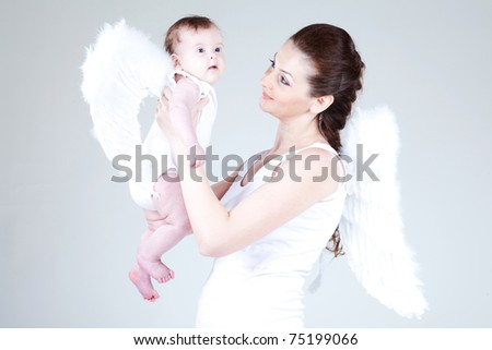 Portrait of a beautiful angelic woman with a child - stock photo