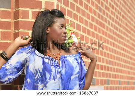 Portrait of a beautiful, approachable, young African American female model, smiling, with flowers