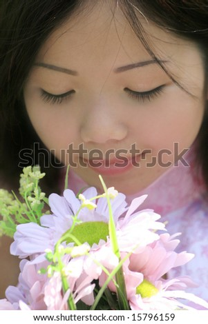 Portrait of a beautiful Asian female with flowers in a summer time, park setting