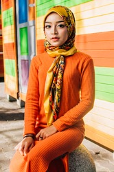 Portrait of a beautiful Asian woman wearing stylish bright outfits with hijab in a real environment. Muslim female hijab fashion portraiture concept.