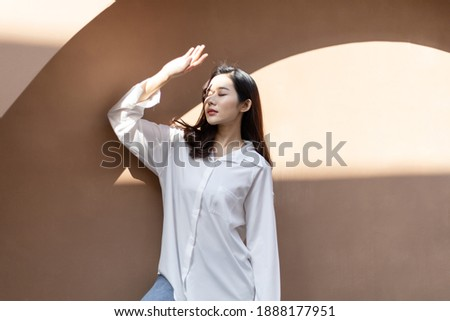 Portrait of a beautiful Asian woman with healthy skin. She uses a sun protection hand that hits her face to protect against UV that has caused her face to dull. Сток-фото ©
