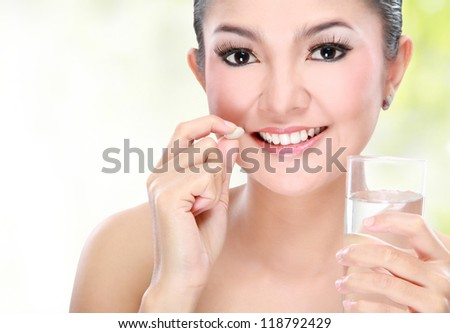 Portrait of a beautiful asian young woman taking vitamin tablet