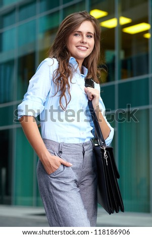 Portrait of a beautiful attractive smiling young businesswoman with briefcase, background
