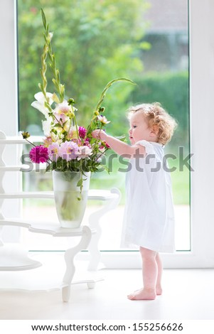 Portrait of a beautiful baby girl playing with fresh flowers wearing a white dress standing next to a window and door to the garden