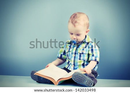 Portrait of a beautiful baby with a book.