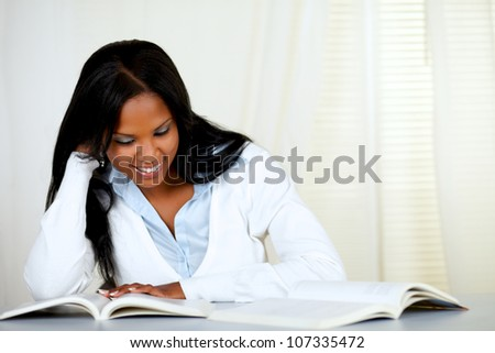 Portrait of a beautiful black woman smiling and reading a book at home indoor