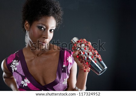Portrait of a beautiful black young woman mixing a cocktail with a cocktail shaker in a dark background.
