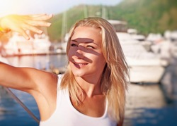 Portrait of a beautiful blond girl covering face by hand of bright sun light, spending weekend on the yacht, happy summer vacation