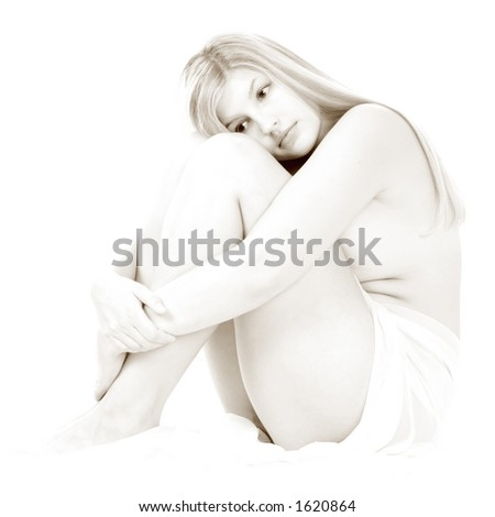 Portrait of a beautiful blond young woman sitting head on her knees - stock photo