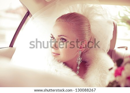 Portrait of a beautiful blonde bride sitting in the wedding car and looking at somebody or something through the window. Wedding day. Daylight