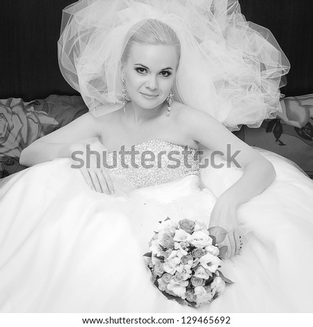Portrait of a beautiful blonde bride with great vapory veil and wedding bouquet. Indoor black and white shot