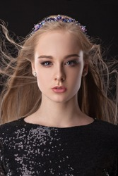 Portrait of a beautiful blonde girl with a diadem and costume jewelry on a black background. Dark clothes. Wind blows