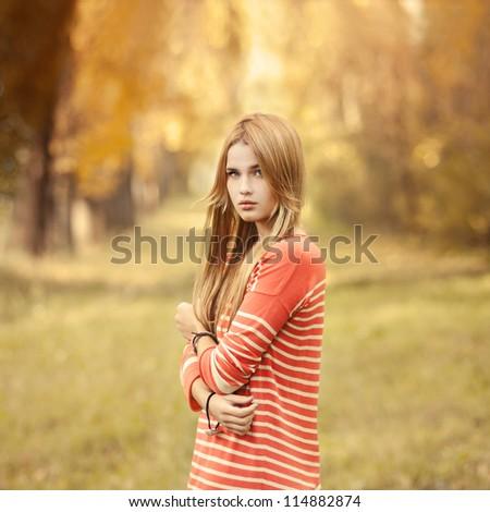 portrait of a beautiful blonde in a park in autumn #114882874
