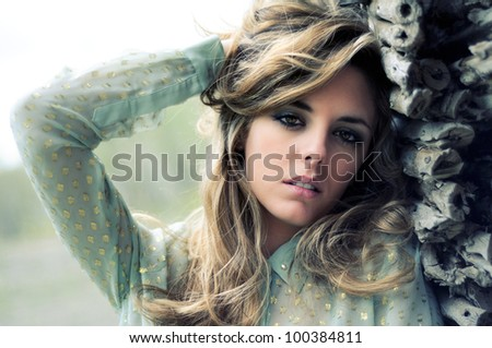 Portrait of a beautiful blonde woman standing by a old wall