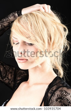 Portrait of a beautiful blonde woman. Studio shot over black background.