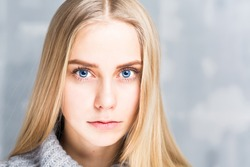 Portrait of a beautiful blonde woman with blue eyes over gray background