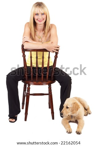 Portrait of a beautiful blonde woman with light blue eyes and colorful make-up sitting on a chair with golden retriever puppy next to her