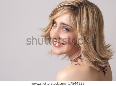 Portrait of a beautiful blonde woman with light green eyes and dramatic make-up on grey background