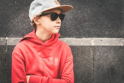 Portrait of a beautiful boy with hat and sunglasses leaning on a black wall. Trendy teen with red sweatshirt looking away arms crossed. Serious young male. Youth, relax positive fashion people concept