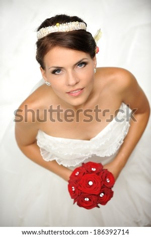 Portrait of a beautiful bride, holding red bouquet of roses.