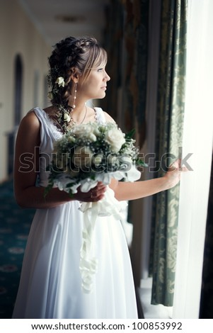 Portrait of a beautiful bride standing near window