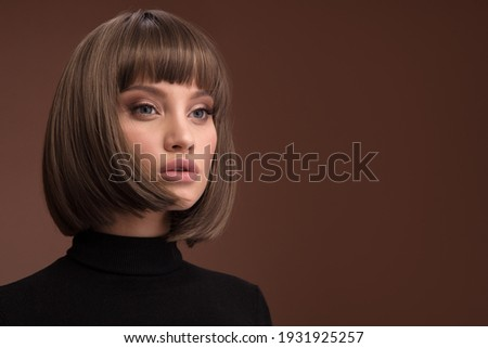 Portrait of a beautiful brown-haired woman with a short haircut on a brown background Stockfoto ©