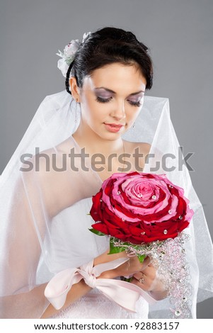 Portrait of a beautiful brunette bride in the studio with a bouquet of re