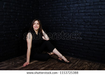 Portrait of a beautiful brunette girl in black jumpsuit sitting and posing in the studio. #1153725388