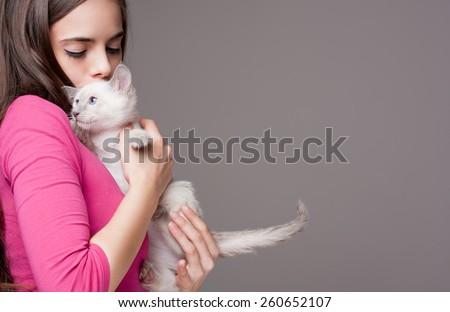 Portrait of a beautiful brunette holding a cute kitten.