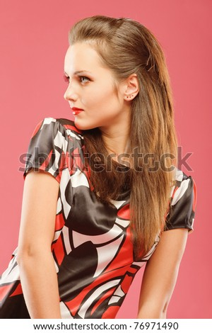 Portrait of a beautiful brunette in a profile on a red background