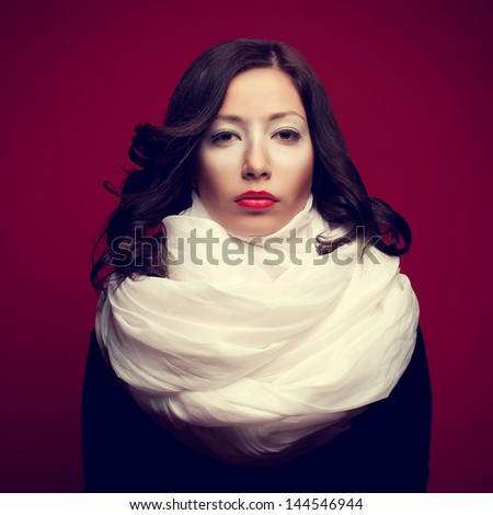 Portrait of a beautiful brunette with arty makeup wearing a vapory white silk scarf  looking like cream (kiss-cake, marsh-mallow) and posing over purple background. Copy-space. Studio shot