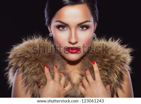 Portrait of a beautiful brunette with classic make up and red lips, holding her hands on fur #123061243
