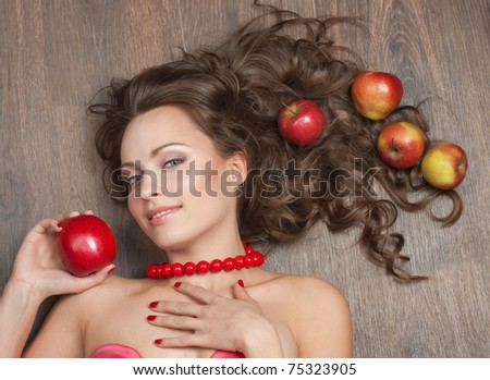 Portrait of a beautiful brunette with red apples