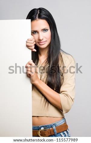 Portrait of a beautiful brunette woman holding a blank white sheet.