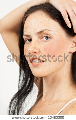 Portrait of a beautiful brunette woman with light blue eyes and freckles on her skin. Not isolated