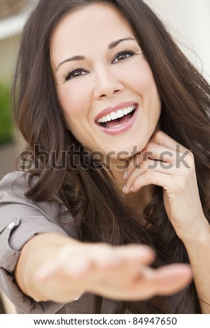 Portrait of a beautiful brunette young woman with perfect teeth smiling laughing and reaching to camera