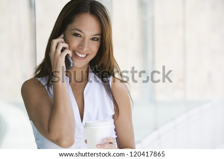 Portrait of a beautiful business woman using cell phone with disposable glass in office break