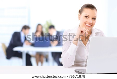 Portrait of a beautiful business woman working on her laptop in an office environment. Colleagues in the background