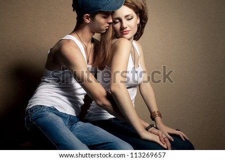 portrait of a beautiful casual couple in jeans sitting together over wooden background. boy hugging girl. studio shot
